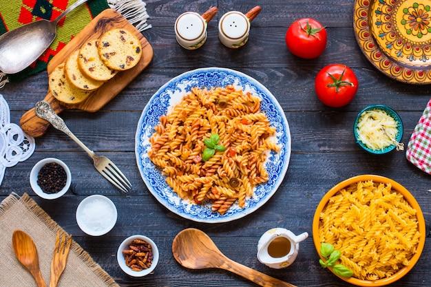 Fusilli pasta met tomatensaus, tomaten, ui, knoflook, gedroogde paprika, olijven, peper en olijfolie op hout