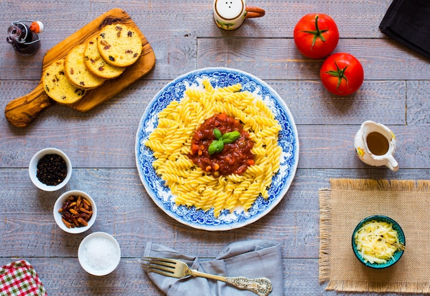 Fusillideegwaren met tomatensaus tomaten knoflook gedroogde paprika olijven peper en olijfolie op een houten achtergrond.