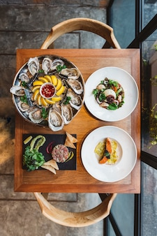 Fusion fine dining maaltijd: verse oester, ravioli in roomsaus met gegrilde zalm