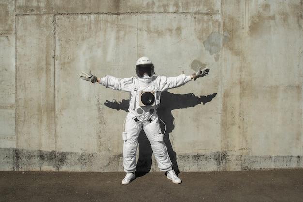 Futuristische astronaut in een helm tegen grijze muren. fantastisch kosmisch kostuum.