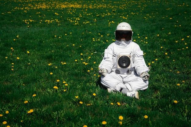 Futuristische astronaut in een helm zit op een groen gazon tussen bloemen in een meditatieve positie.