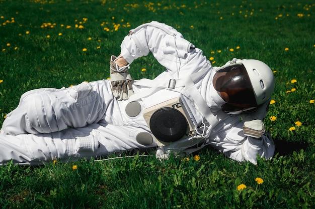 Futuristische astronaut in een helm zit op een groen gazon tussen bloemen.