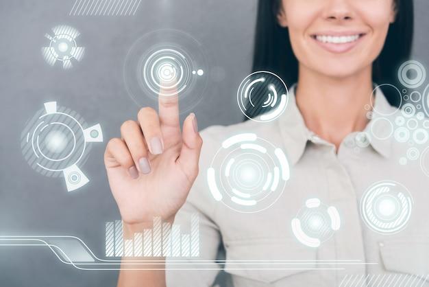 Futuristische technologieën. bijgesneden afbeelding van jonge vrouw die transparant scherm aanraakt en glimlacht