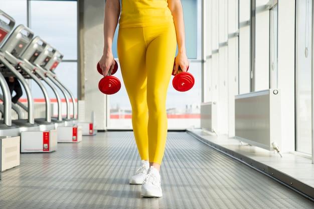 Fysiek fit vrouw in de sportschool met halters klaar om haar armen en biceps te versterken
