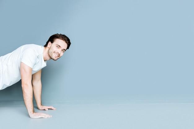 Fysieke activiteit. aardige, sterke, bebaarde man die lacht en pushups doet terwijl hij aan het sporten is