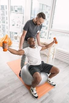Fysieke activiteit. aardige sterke man die achterover leunt tijdens een oefening op de medball