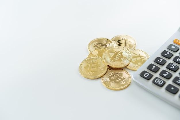 Fysieke gouden bitcoin - btc-munten op de witte tafel met rekenmachine close-up met copyspace. bitcoin en rijkdom in het investeringsconcept voor digitale activa. cryptocurrency uitwisseling.