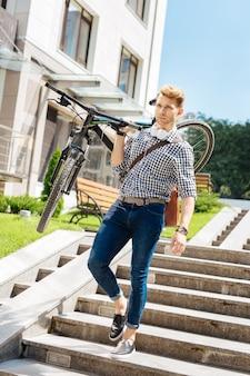 Fysieke kracht. aardige knappe man die zijn fiets draagt terwijl hij de trap afloopt