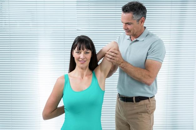 Fysiotherapeut begeleiden zwangere vrouw met oefening voor schouder en rug