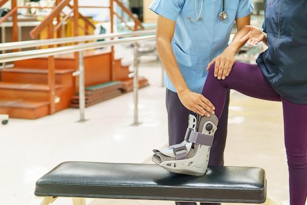 Fysiotherapeut controleert de knie van de patiënt in de kliniek.