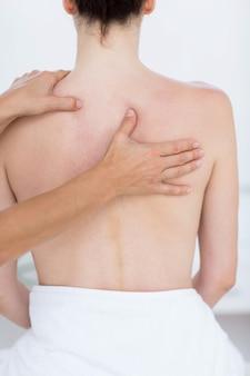 Fysiotherapeut die achtermassage in medisch bureau doet