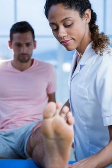 Fysiotherapeut die beenmassage geeft aan een mens