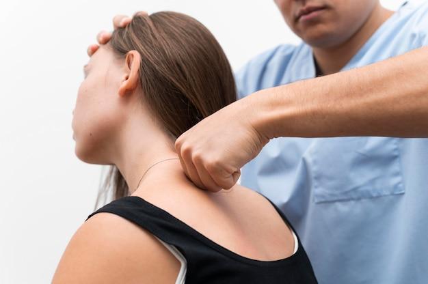 Fysiotherapeut die de bovenrug van de vrouw masseert