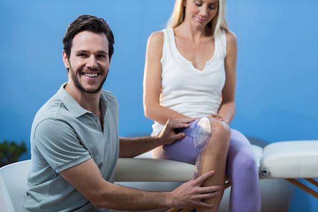 Fysiotherapeut die de knie van vrouwelijke patiënten met goniometer onderzoeken