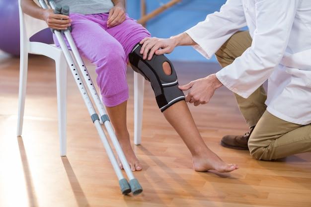 Fysiotherapeut die de knie van vrouwelijke patiënten onderzoeken