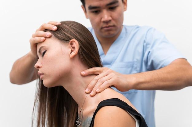 Fysiotherapeut die de nek van de vrouw masseert