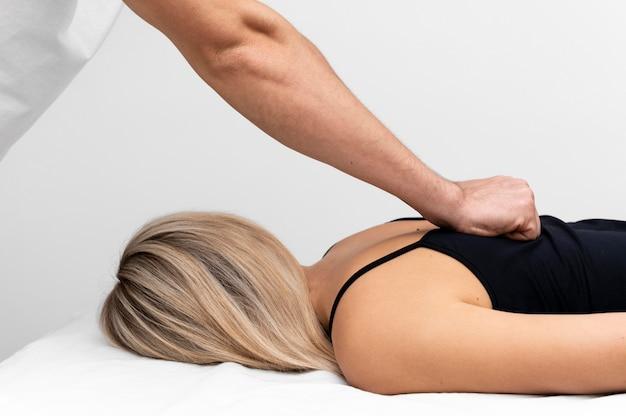 Fysiotherapeut die de rug van de vrouw masseert