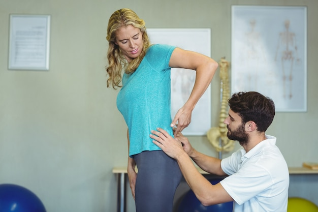 Fysiotherapeut die de rug van de vrouw onderzoekt