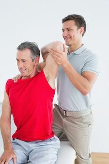 Fysiotherapeut die een glimlachende rijpe bemant wapen uitrekt
