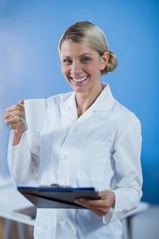 Fysiotherapeut die een medisch rapport houden terwijl het hebben van koffie
