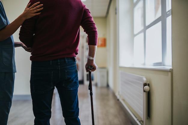 Fysiotherapeut die een patiënt opleidt om opnieuw te lopen