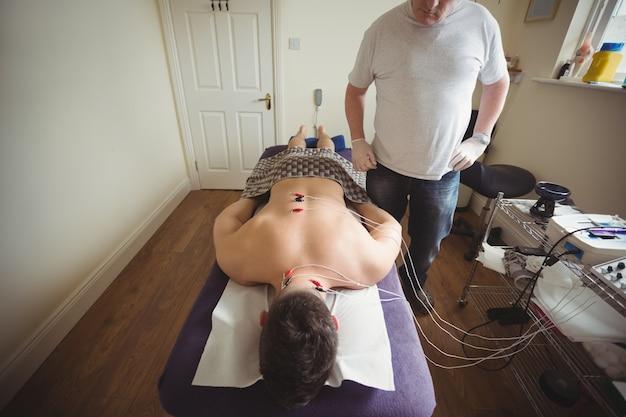 Fysiotherapeut die elektro droge needling op de rug van een patiënt uitvoeren