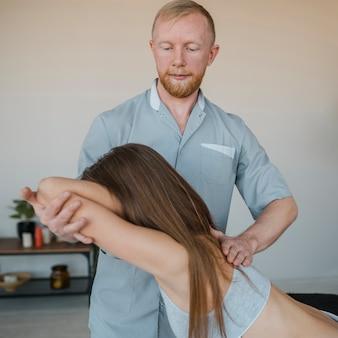 Fysiotherapeut die fysieke oefeningen doet met vrouwelijke patiënt