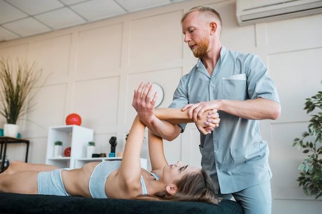 Fysiotherapeut die fysieke oefeningen op vrouwelijke patiënt uitvoert