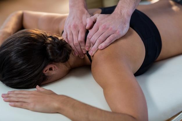 Fysiotherapeut die fysiotherapie geeft aan de nek van een vrouwelijke patiënt