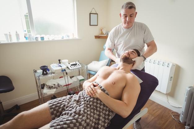 Fysiotherapeut die hals van een patiënt onderzoekt
