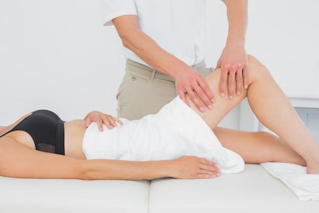 Fysiotherapeut die het been van een jonge vrouw onderzoeken