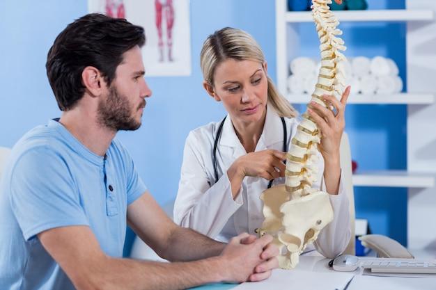 Fysiotherapeut die het wervelkolommodel aan patiënt uitlegt