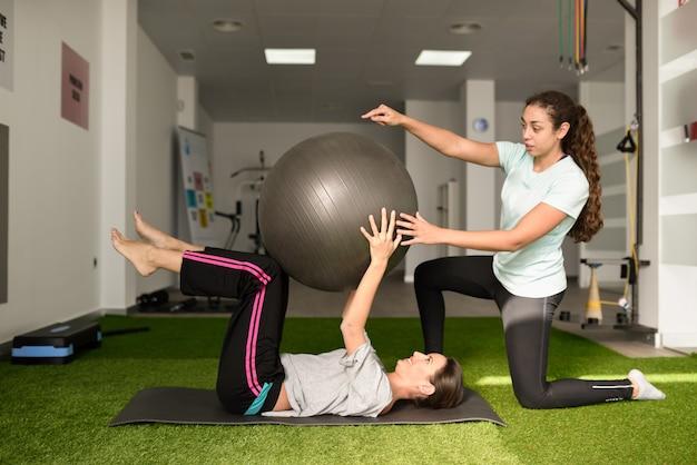 Fysiotherapeut die jonge kaukasische vrouw met oefening bijstaan