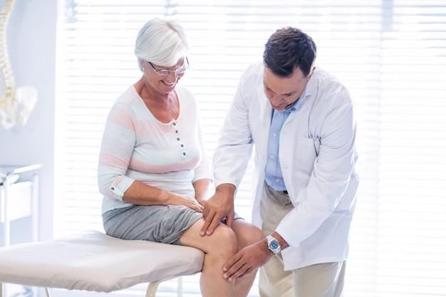 Fysiotherapeut die knietherapie geven aan hogere vrouw