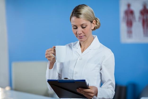 Fysiotherapeut die medisch rapport bekijken terwijl het hebben van koffie