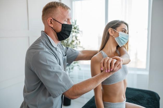 Fysiotherapeut die medische masker draagt tijdens een therapiesessie met vrouwelijke patiënt