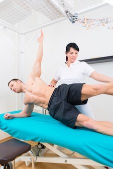Fysiotherapeut die met patiënt in de praktijk uitoefent