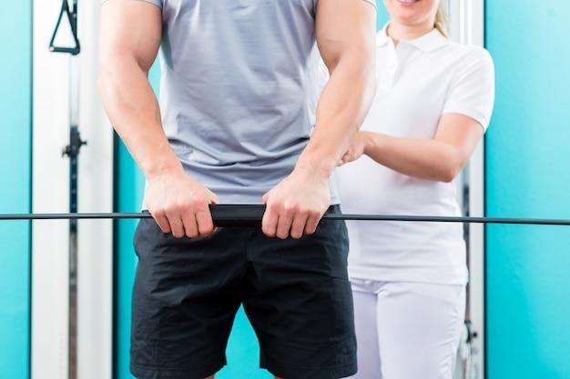 Fysiotherapeut die met patiënt in de praktijk werken