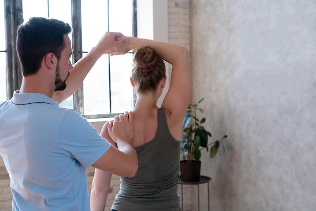 Fysiotherapeut die middellange opname van de patiënt controleert