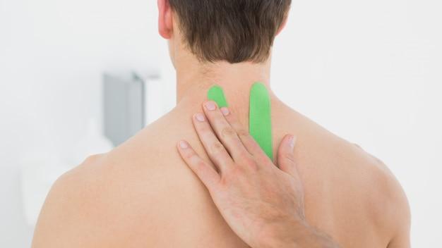 Fysiotherapeut die op groene kinesioband op patiëntenrug zet