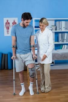 Fysiotherapeut die patiënt helpt met krukken te lopen