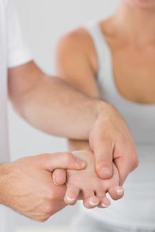 Fysiotherapeut die patiëntenhand onderzoekt