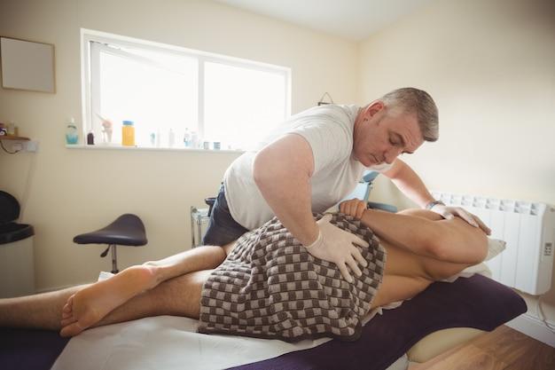 Fysiotherapeut die rug van een patiënt onderzoekt