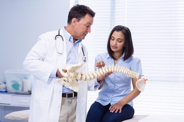 Fysiotherapeut die ruggengraatmodel aan patiënt uitlegt
