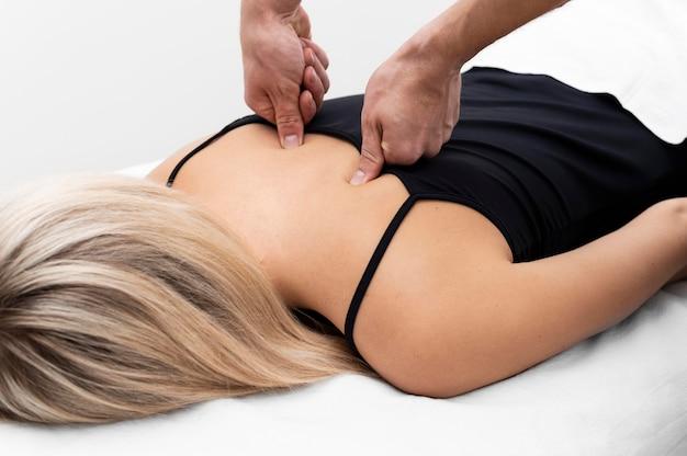 Fysiotherapeut die rugmassage op vrouwelijke patiënt uitvoert