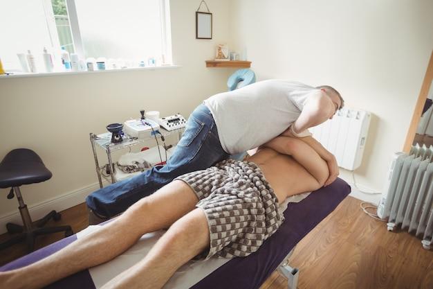 Fysiotherapeut die schouder van een patiënt onderzoekt