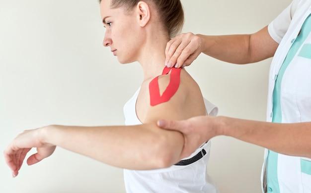 Fysiotherapeut die therapie ondergaat met een vrouwelijke patiënt