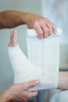 Fysiotherapeut die verband op gewonde voeten van patiënt zet