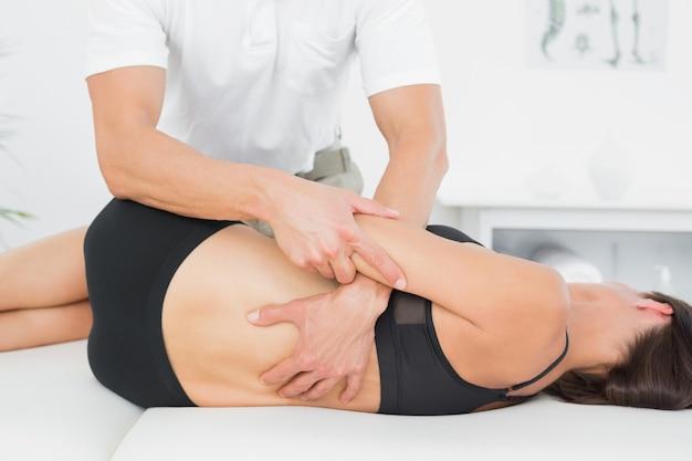 Fysiotherapeut die vrouw terug in medisch bureau masseren