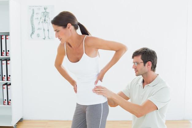 Fysiotherapeut die vrouw terug in medisch bureau onderzoeken